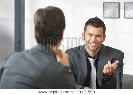 Young businessman sitting on sofa at office talking to businesswoman, smiling.