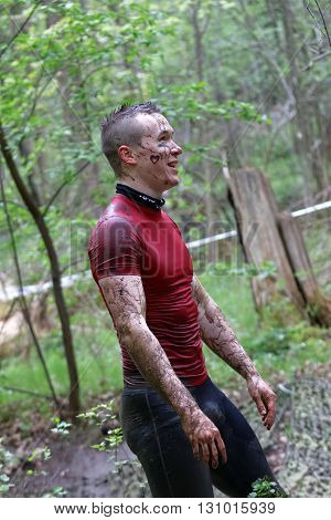 STOCKHOLM SWEDEN - MAY 14 2016: Smiling muscular man in red shirt covered with mud in the obstacle race Tough Viking Event in Sweden April 14 2016