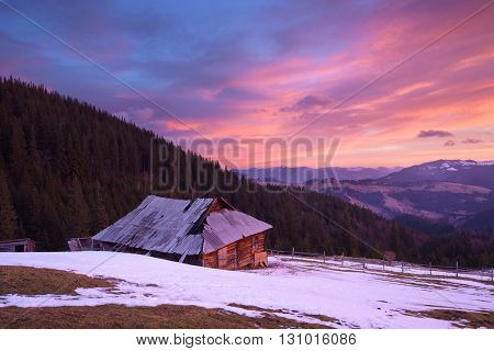 Old house in mountain village. Beautiful clouds in morning sky. Spring landscape. Carpathians, Ukraine, Europe