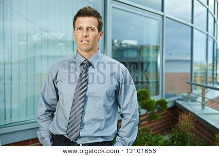 Businessman standing on office terrace outdoor, looking at camera, smiling.