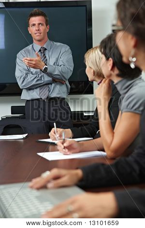 Businessman conducting business training, people sitting in a row, listening.