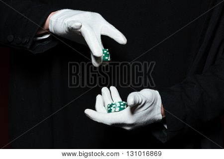Hands of man magician in white gloves holding green casino chips over black background