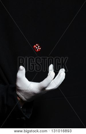 Hand of man magician in white glove showing tricks using one flying dice over black background