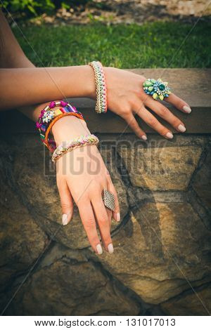 closeup of female hands with colorful  ring and bracelets on stone