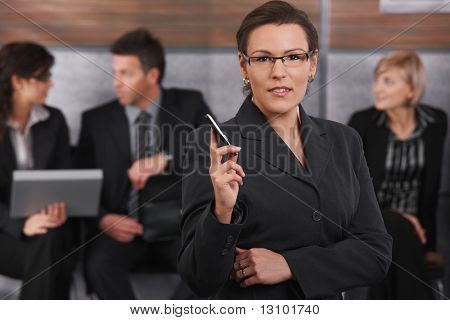 Portrait of mid-adult businesswoman standing in office lobby, holding mobile phone, looking at camera, smiling.