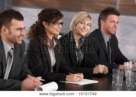 Attractive young businesswoman sitting at table on business seminar together with colleagues, looking at camera, smiling.