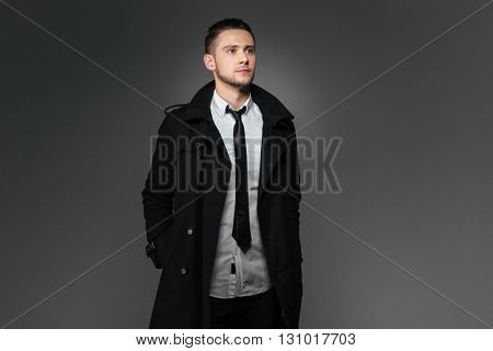 Attractive young businessman in black coat standing with hands in pockets over grey background