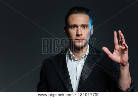 Portrait of confident young man magician with raised hand over grey background