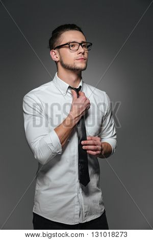 Serious young businessman in glasses, white shirt and tie over grey background