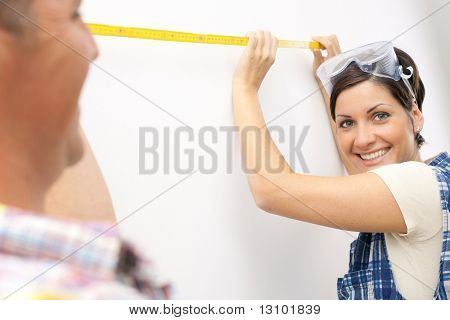 Young woman smiling at camera holding measuring stick in focus, man laughing.