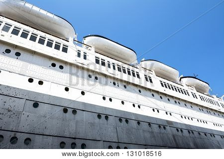The hull of an old cruise ship shows the puzzled detail of massive metal plates and rivets that make up the ship's main structure