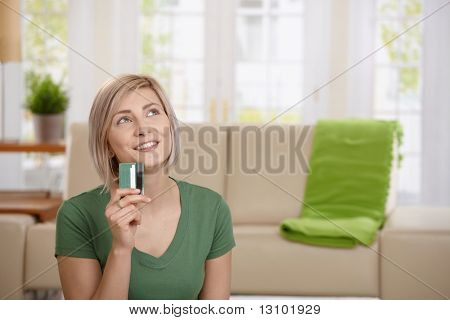 Young woman at home holding credit card looking up thinking about shopping.