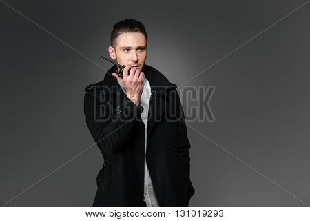 Serious young man in black coat talking in walkie talkie over grey background