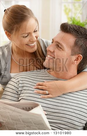 Happy couple sitting at home looking at each other, man holding newspaper, smiling.