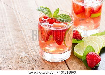 fresh lemonade with strawberries lime and mint on a wooden background