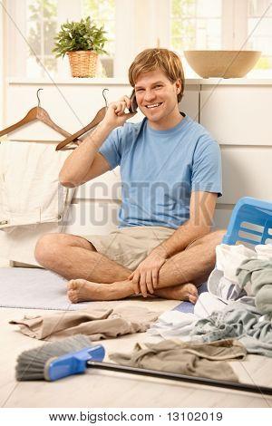 Glücklich Kerl sitzt am Boden des Wohnzimmers sprechen auf Handy, Blick in die Kamera statt th