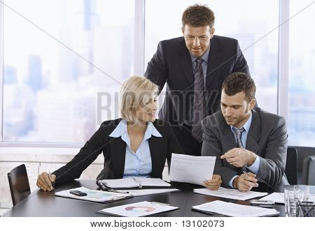 Businesspeople reviewing documents together in office.