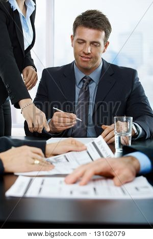 Smiling executive signing contract in office, assistant pointing at paper,