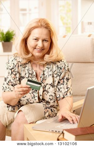 Senior woman smiling at camera while shopping online, holding creditcard and typing on computer keyboard.