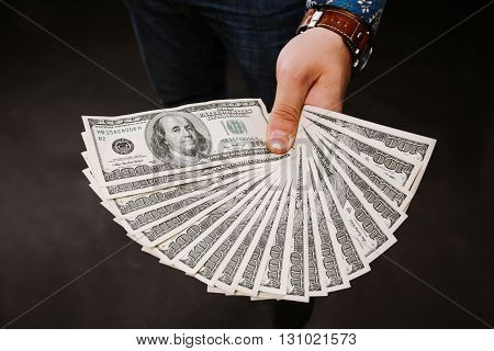 Hand holding a fan of dollars. One hundred dollars banknotes bundle, lot dollars, lot of banknotes
