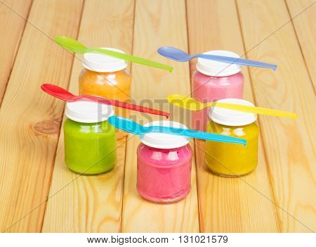 Baby puree in jars and colorful plastic spoons on a background of light wood.