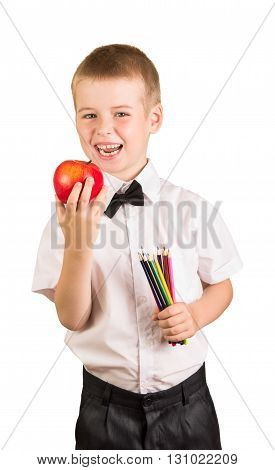 Happy schoolboy holding a pencil and an apple isolated on white background.
