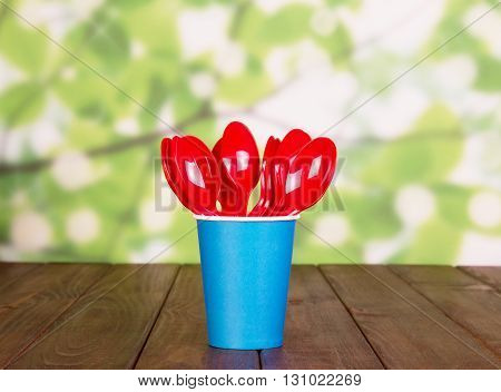 Disposable cups and plastic spoons on an abstract green background.