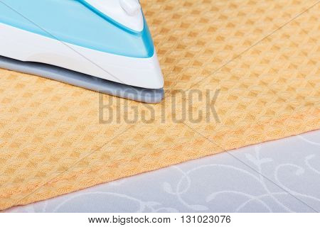 Part of the steam iron, towel on abstract light gray background.