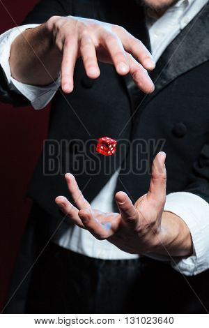 Closeup of hands of young man magician making red dice flying in the air  over dark background