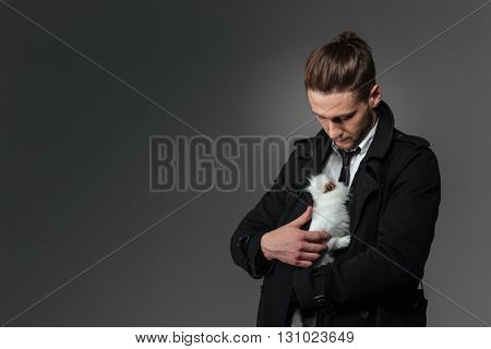 Attractive young businessman standing and holding rabbit  over grey background