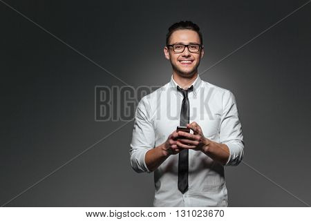 Happy young businessman standing and using smartphone over grey background