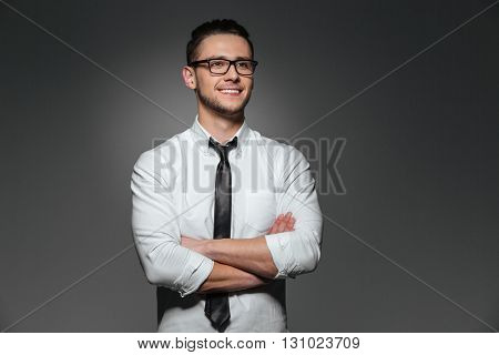 Smiling young businessman in glasses standing with arms crossed over grey background