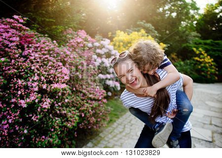 Young woman playing with boy 8-9 years old in the park. Both laugh. They are surrounded by picturesque greenery