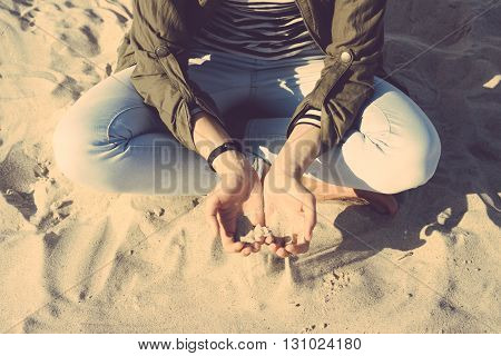 Woman in coat and jeans sitting on the beach cross-legged in her palms sand. Top view yellow toning.