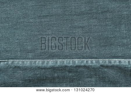 denim or rough cotton fabric or jeans material with the stitched seam for the textile textured background of pale indigo color