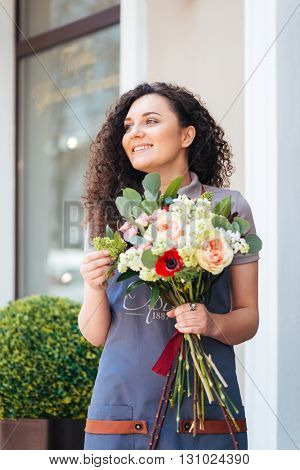 Happy charming young woman florist standing in front of shop and holding flower bouquet