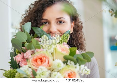 Happy cute curly young woman holding bouquet of flowers and smiling