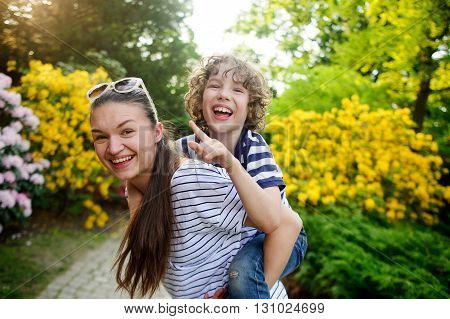 Young woman playing with boy 8-9 years against a background of flowering garden. They are very fun