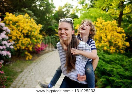 Young woman carries on the shoulders of 8-9 year-old boy. They are very fun. Behind them are picturesque flowering garden