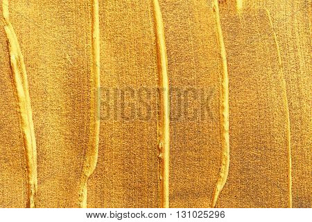 Golden shining stroke texture made with brush and paint hand drawn. Golden abstract background. Place for text.