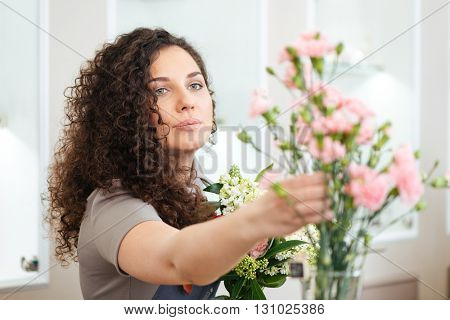 Beautiful concentrated young woman florist taking flowers and making bouquet in shop