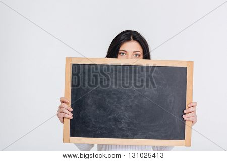 Beautiful young brunette girl covers her face with blank chalkboard, isolated on white background