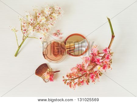 There White and Pink  Branches of Chestnut Tree,Bronze Powder with Mirrow and Make Up Brush are on White Table,Top View.Toned