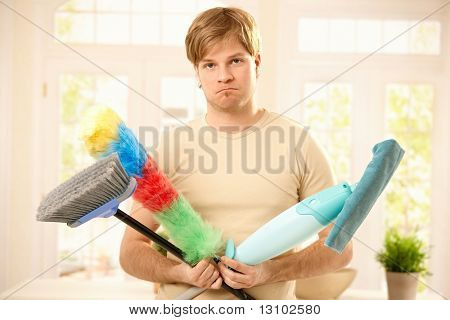 Portrait of guy upset with housework, holding broom, mop and flannel in bright living room.