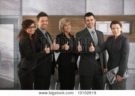 Portrait of happy successful business team showing thumbs up to camera in office.