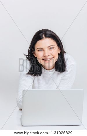 Cheerful young brunette girl using laptop, isolated on white background