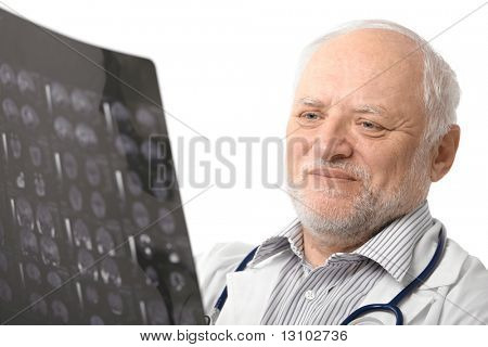 Portrait of happy senior doctor looking at X-ray image, smiling. Isolated on white background.