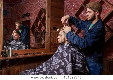 Barber combs client Barbershop. The master is working on a way the client.