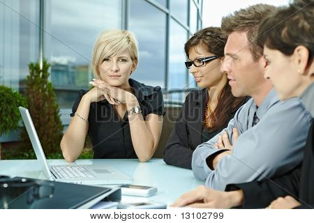 Group of young business people sitting in a row at table on office terrace outdoor, talking and working on laptop computer.