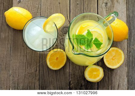 Pitcher And Glass Of Lemonade With Lemon Slices And Mint, Downward View On A Rustic Wood Background